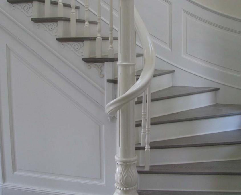 Viertelgewendelte Treppe mit Setzstufen, Stufen grau gebeizt und geölt, Wangen deckend weiß lackiert, gedrechselte Säule mit geschnitztem Sockelteil, Ornamente, Handlaufkrümmling, Wandverkleidungen mit Füllung