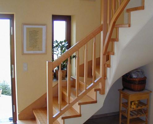 viertelgewendelte Betontreppe, belegt mit Stufen und Setzstufen in Buche Massivholz, Geländer Rechteckstäbe mit angedrehten Zapfen und Untergurt
