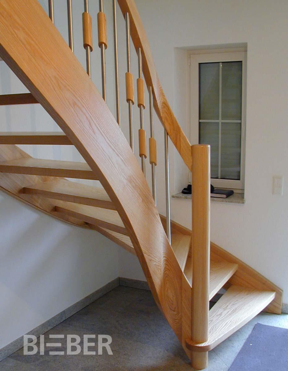Viertelgewendelte Treppe Massivholz Esche, Lichtwange (außen) mit liegendem Krümmling, gerundete Antrittstufe, Antrittsäule rund, Geländerstäbe Holz-Edelstahl-Kombination