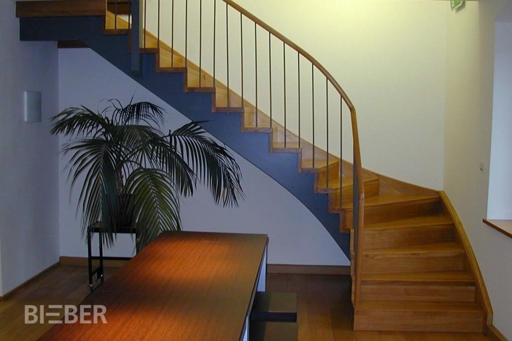 Viertelgewendelte Betontreppe, belegt mit Massivholzstufen Eiche, Wandwange Eiche massiv, Lichtwange aufgesattelt und farbig lackiert, Geländer mit Rundhandlauf und Stahlstäben Projekt: Rathaus Hartha
