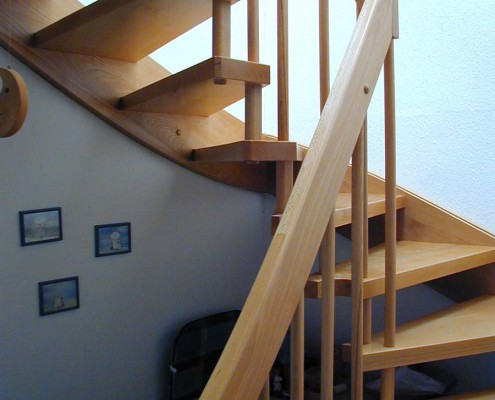 Halbgewendelte Treppe in Esche Massivholz, Wandseite eingestemmte Wange, Lichtseite verbolzt, Geländer Rundstäbe