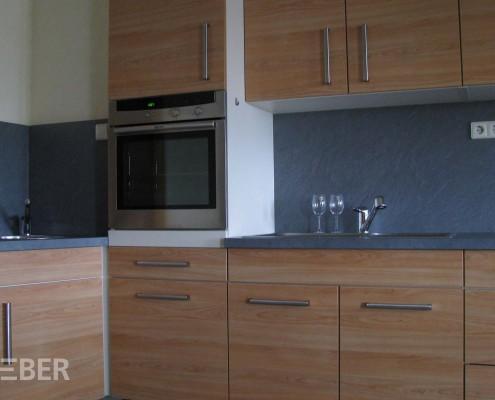 Einbau-Küchenmöbel, bestehend aus Unterschränken mit Ceran-Kochfeld und Einbau-Spüle, Hochschrank mit Einbau-Backofen, Waschtisch, Hängeschränke mit eingebautem Dunst-Abzug, separater Geschirr- und Vorratsschrank, Front Kirschbaum Dekor, Arbeitsplatte Schiefer Dekor