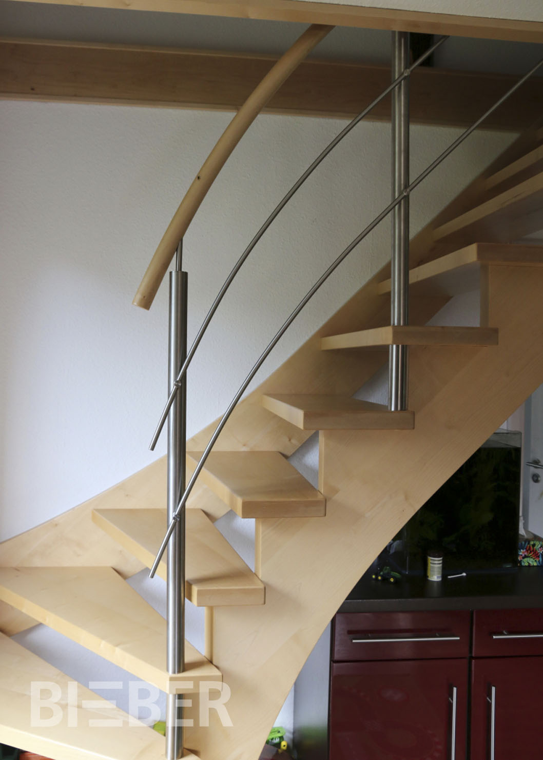 Viertel gewendelte offene Treppe in Massivholz Ahorn, Lichtseite aufgesattelt, mit Wandwange, Geländerpfosten Edelstahl, waagerechte Füllstäbe Edelstahl