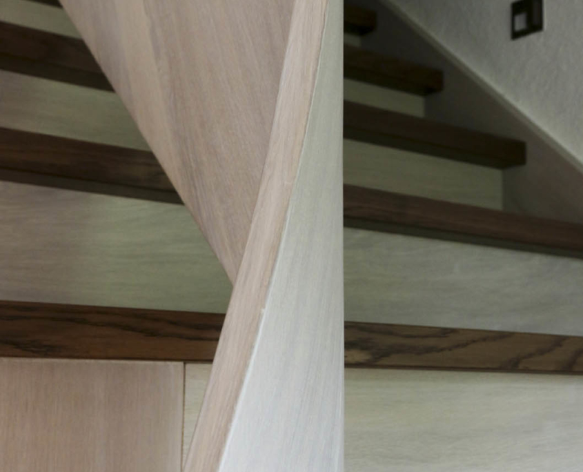 Aufgesattelte Treppe in Massivholz Eiche viertelgewendelt, mit gebogenem Geländer aus Brettschichtholz, Oberfläche mit hell und dunkel pigmentiertem Lack
