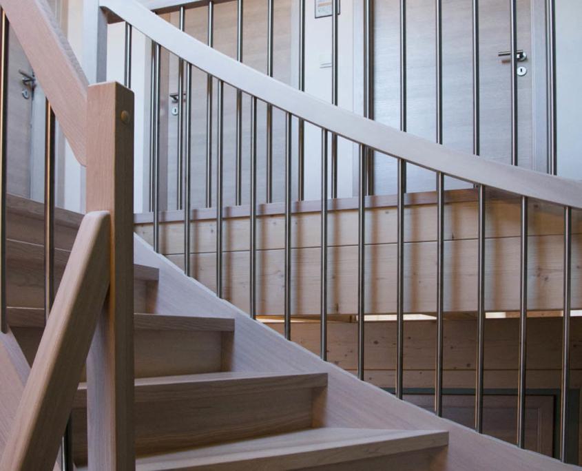 Treppe Massivholz Esche als Wangentreppe, halbgewendelt mit Setzstufen, gebeizt mit weiß pigmenierter Ölbeize, Edelstahlgeländer